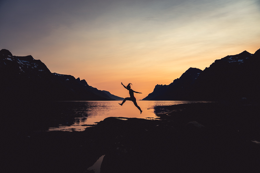 Kvinne hopper i solnedgang i Ersfjorden