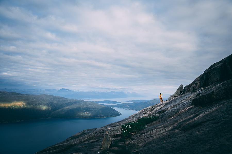 Dame nyter utsikten over Tromsø fra et fjell