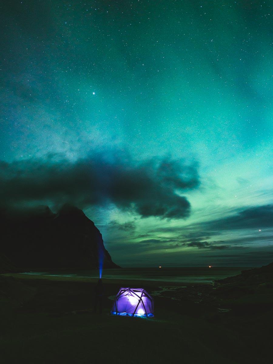 Mann står ved siden av et telt og ser på nordlyset