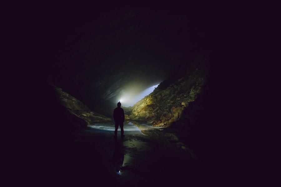 Mann står inne i en grotte og lyser opp omgivelsene med hodelykt