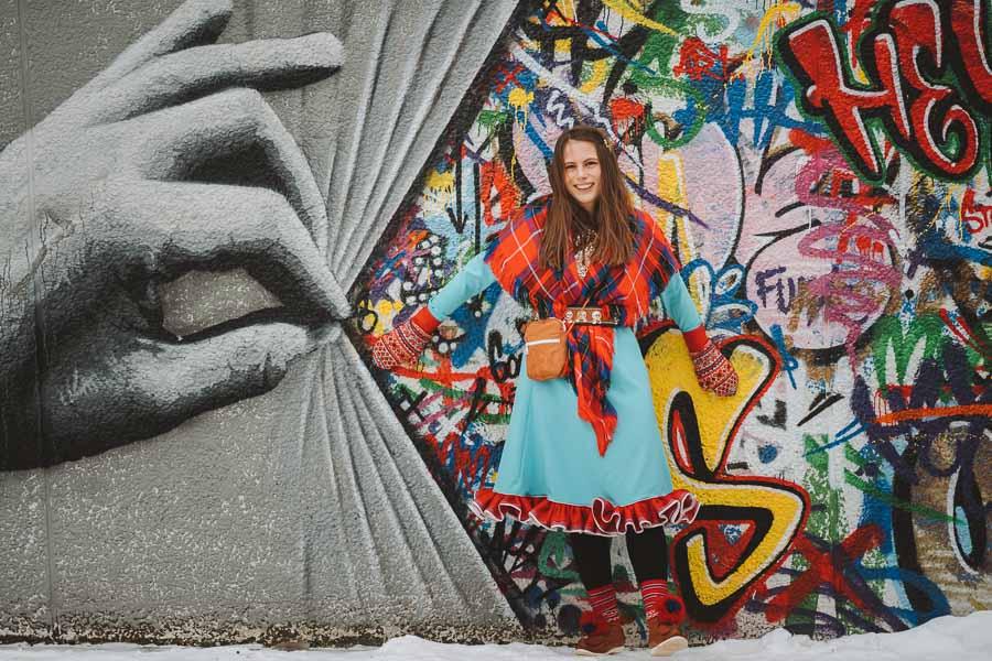 Samisk kvinne står foran fargerik vegg