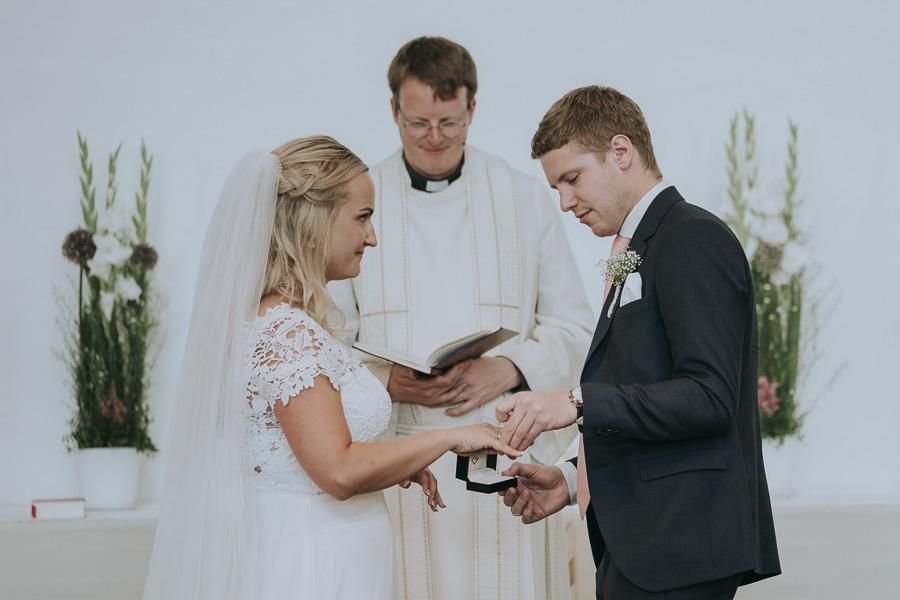 Brudgommen setter ring på fingeren til bruden i et bryllup