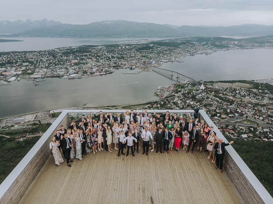 Dronebilde av alle gjestene i bryllup med Tromsø i bakgrunn