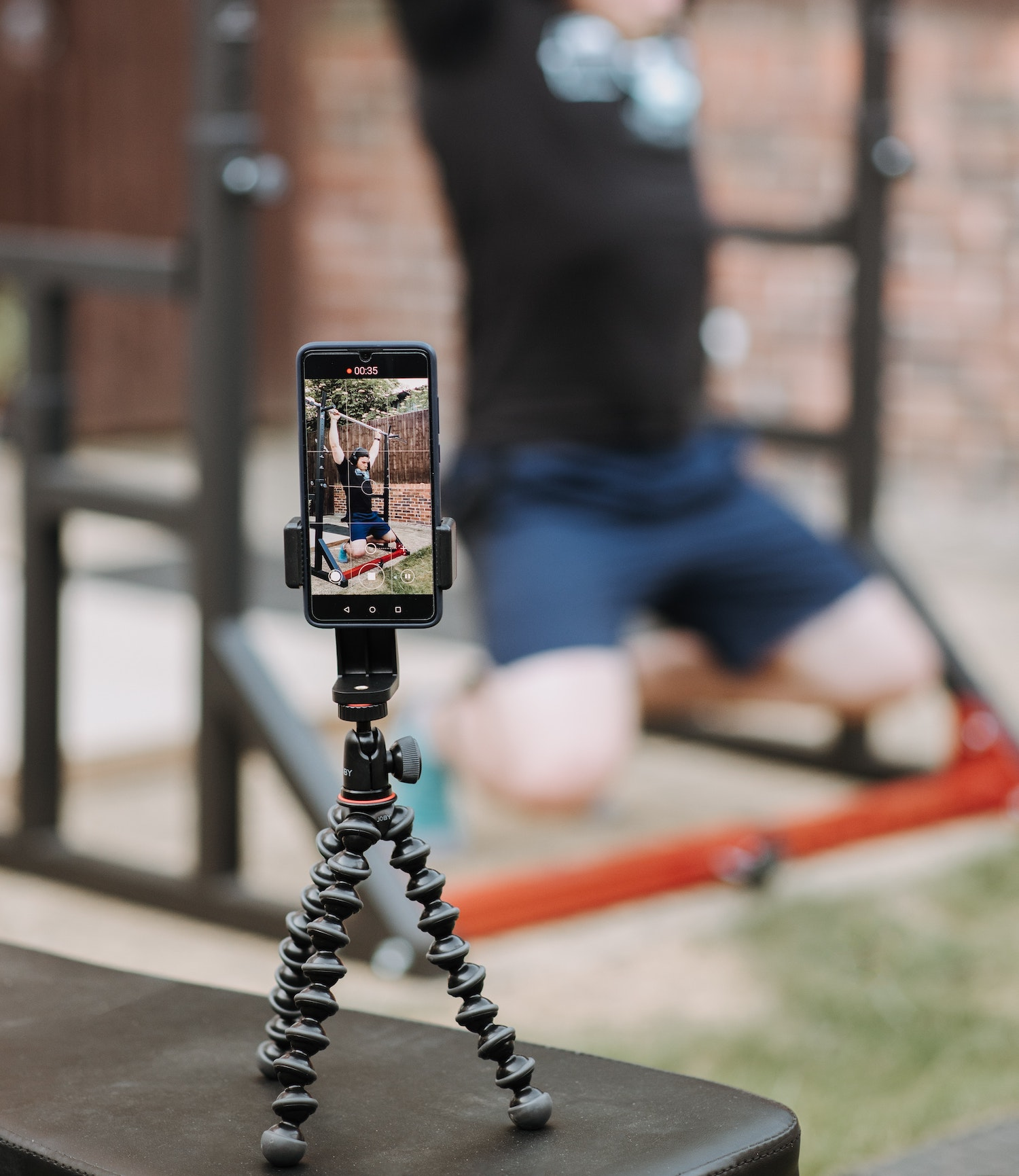 Phone on tripod recording man working out