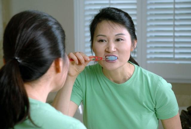 Woman brushing her dental implnats