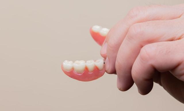 Hand holding dental implants model