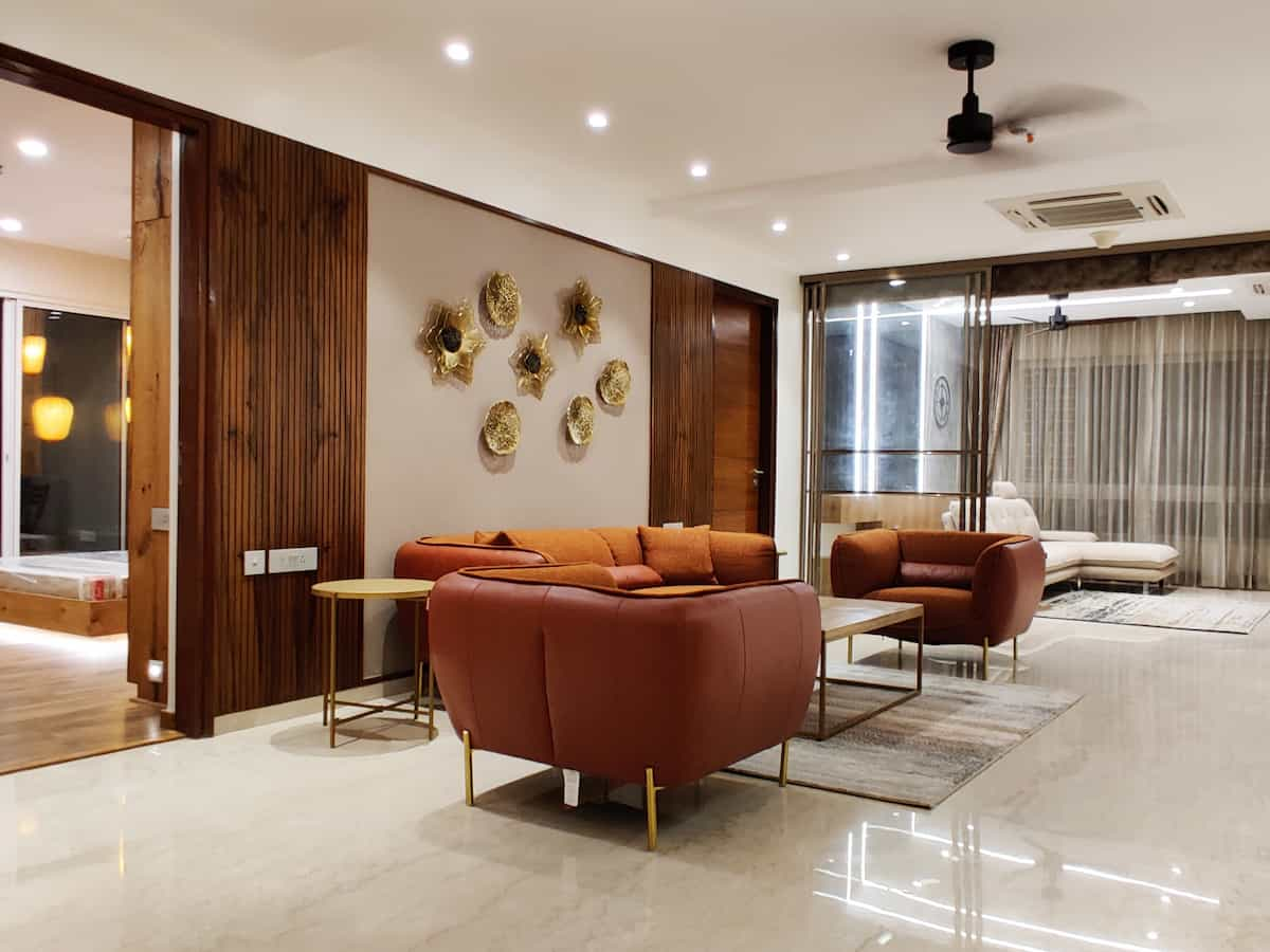 Living room interior design with sofa and wall paper behind, along with the paneling in veneer