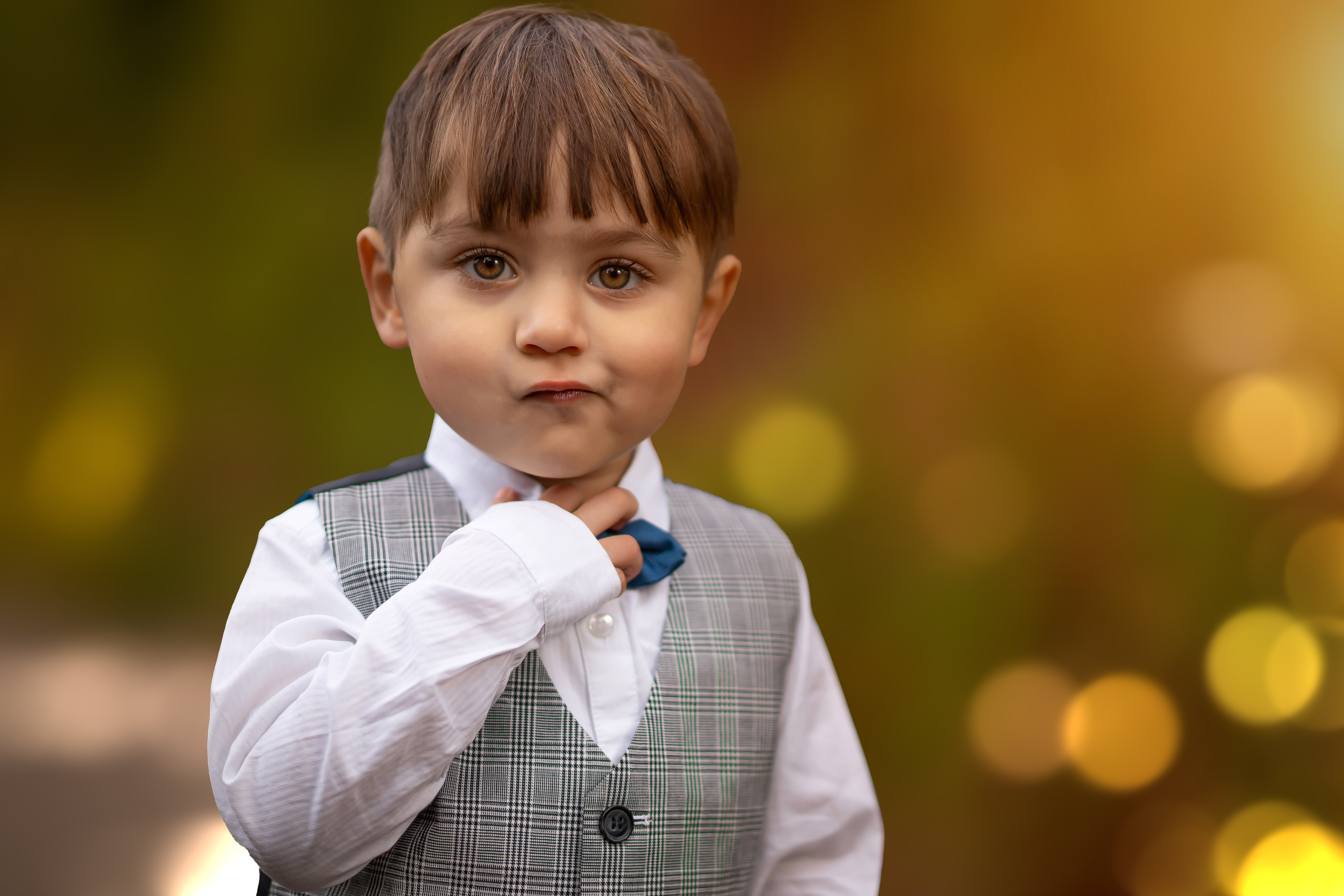 Photography of child in a park with bokeh in the background holding is bow tie