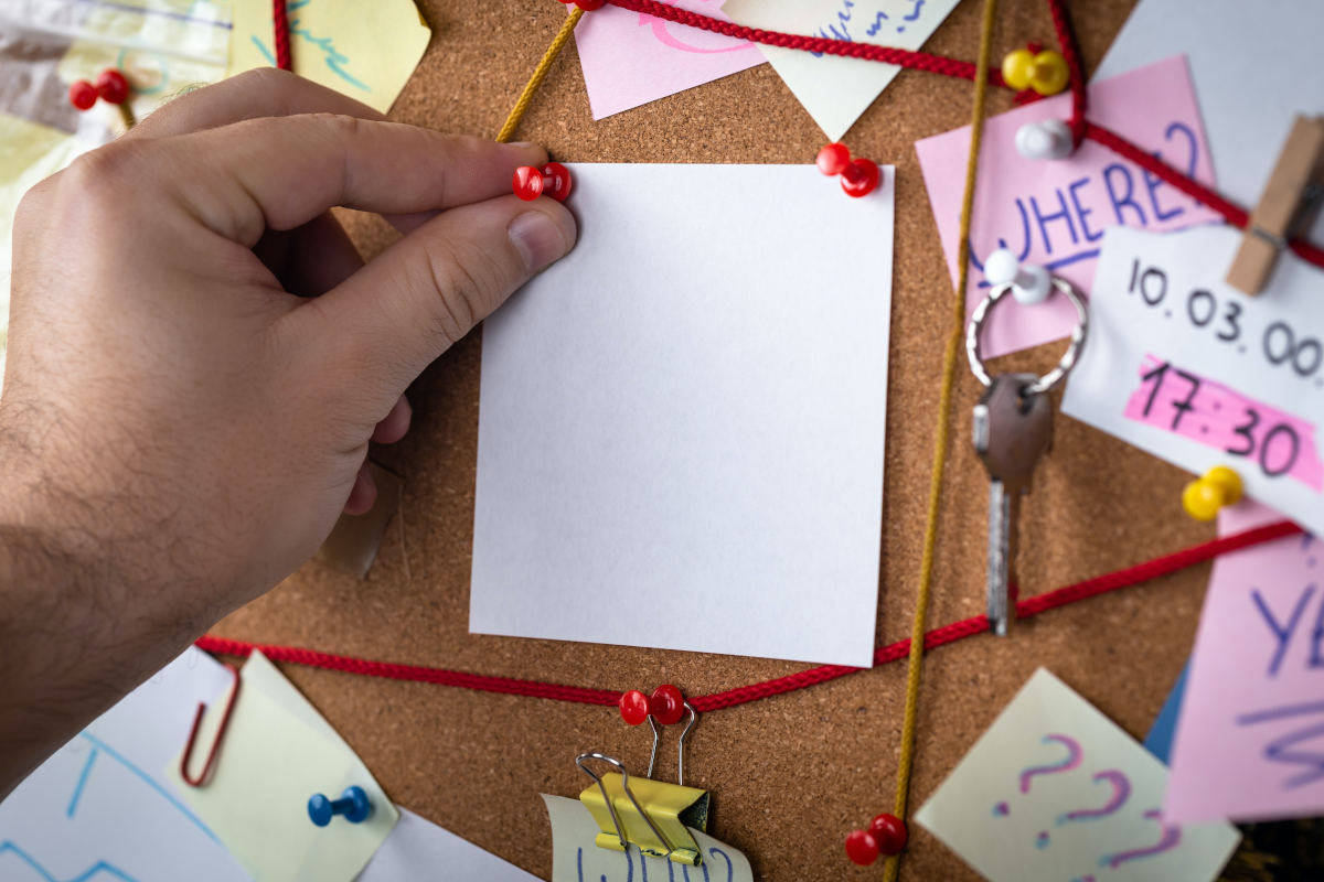 A hand comes in from out of frame and pins a paper to a cork board.