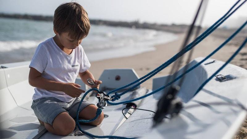 Un enfant préparant sur la plage son dériveur