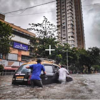Two men pushing a car in a flood