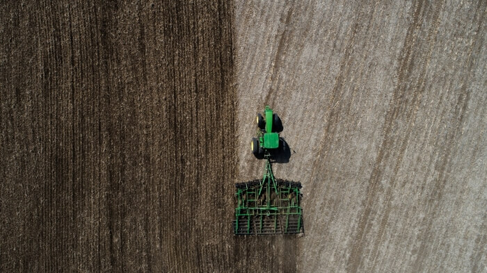A tractor tilling a field from above