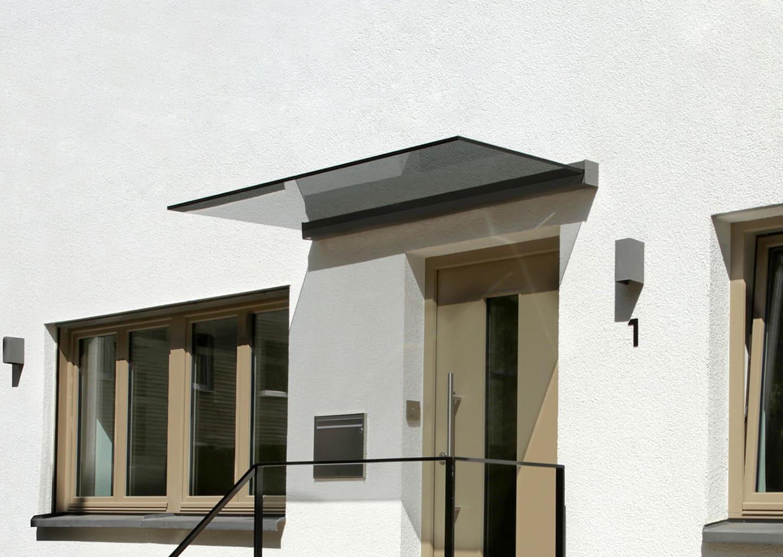 Der Einbau unseres Glasvordaches PLAN FIVE: eine rahmenlose und elegante Eingangsüberdachung.