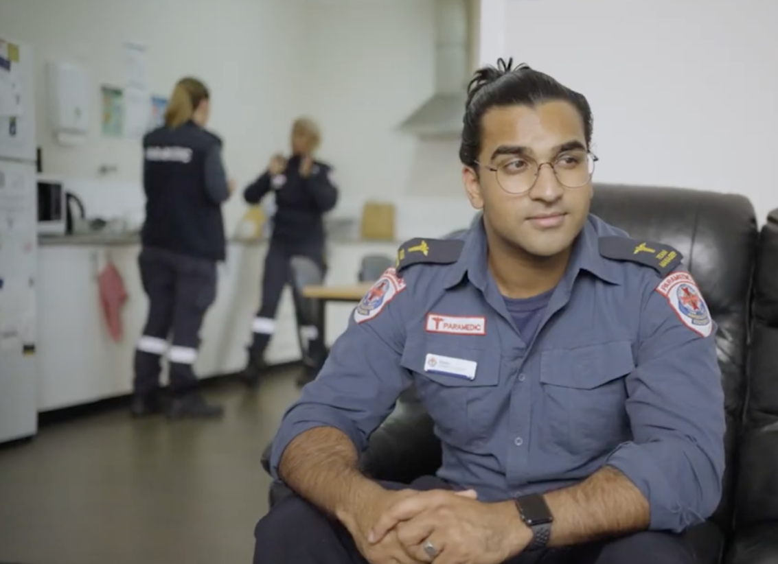 A Firefighter sat on a sofa in his uniform, colleagues are standing chatting in the background