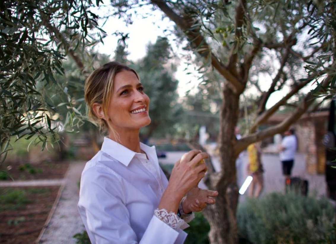 Picture of Princess Tatiana standing out doors in an orchard, wearing a white blouse.