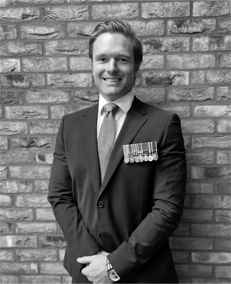 Picture of Nathan Jones smiling and looking into the camera. He is wearing a suit with medals pinned to the pocket.
