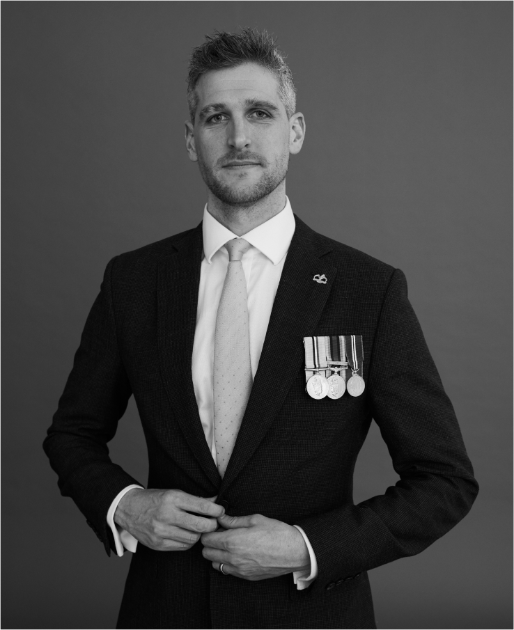 Picture of David wiseman in black and white. He wears a suit with many medals pinned to it