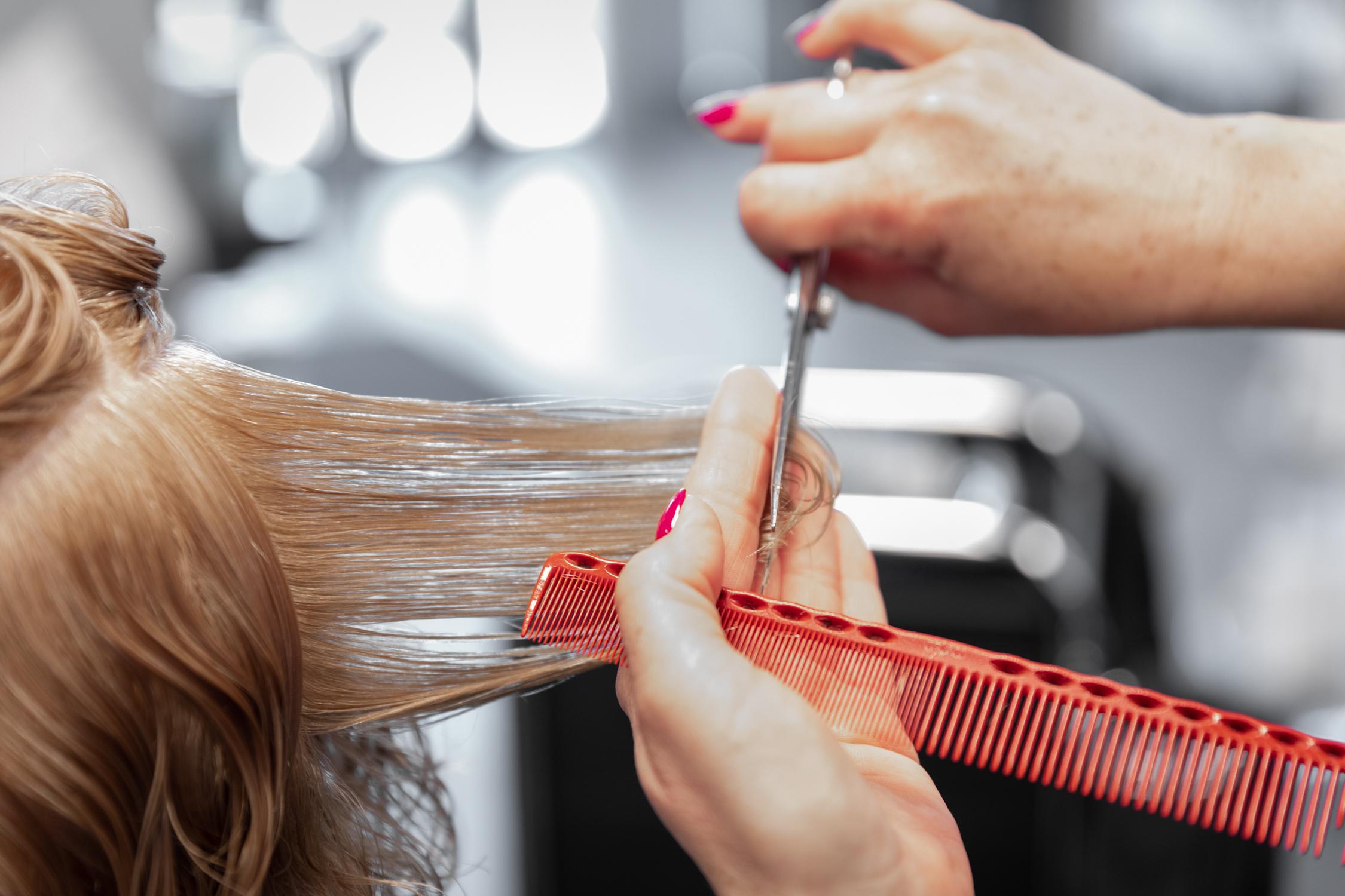 Haare schneiden mit Kamm und Schere bei Mira Schmitt Friseure.