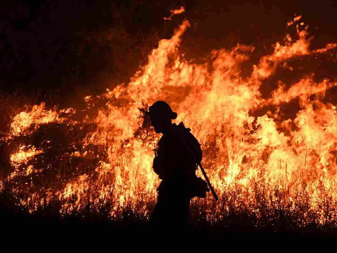 Silhouette of firefighter with flames behind