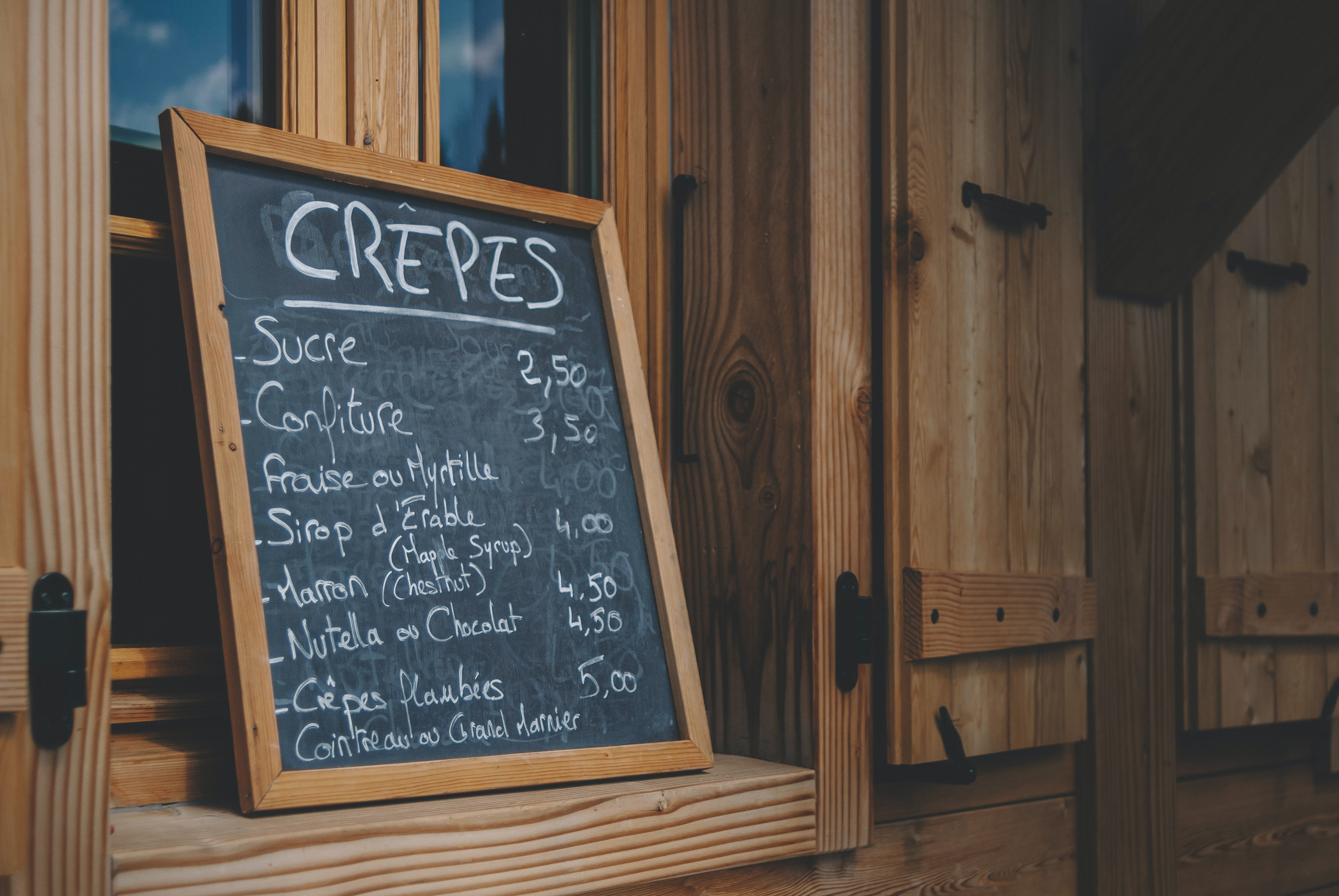 Chalkboard sign in wooden frame with crepes menu written