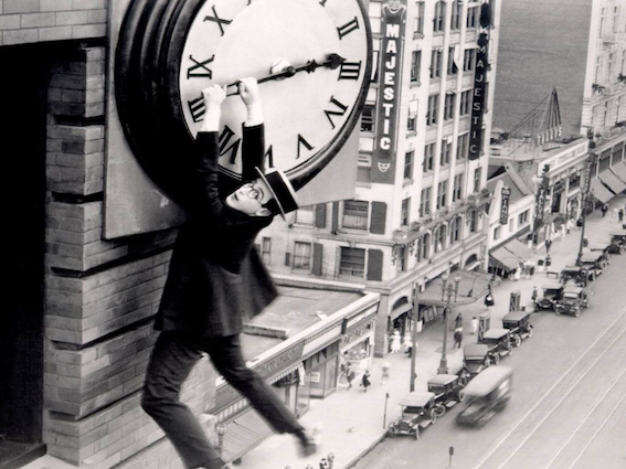 Black and white shot of a man holding onto a clock hand for dear life (circa 1920's)