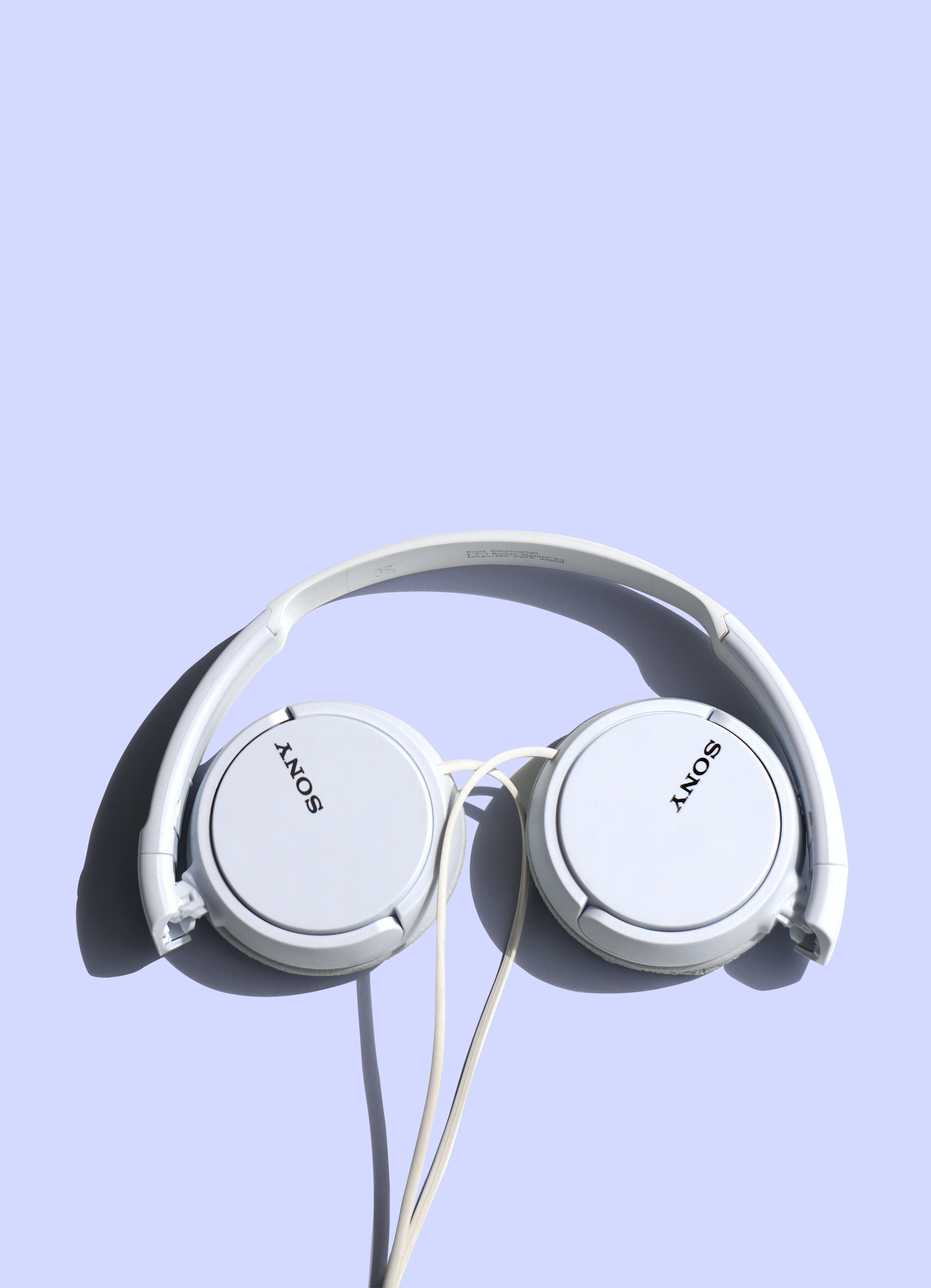 A pair of white headphones on a violet background