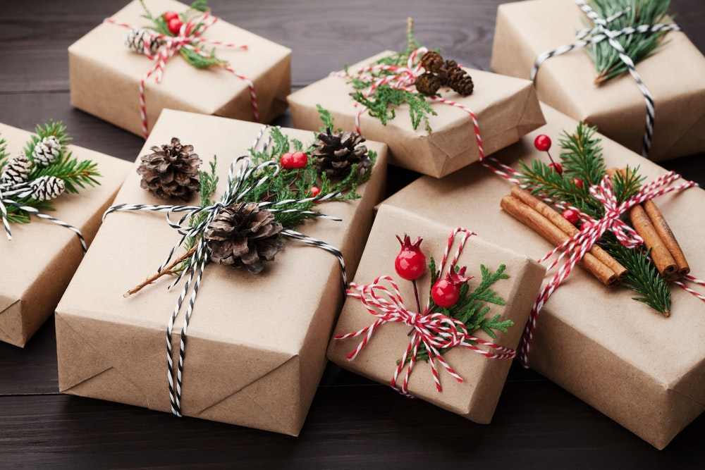 A pile of presents wrapped in brown paper with mistletoe