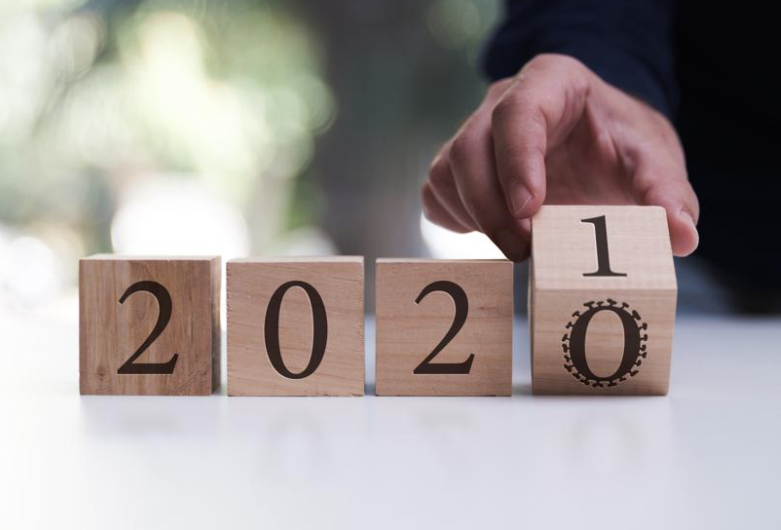 Hand turning a number block from 2020 to 2021