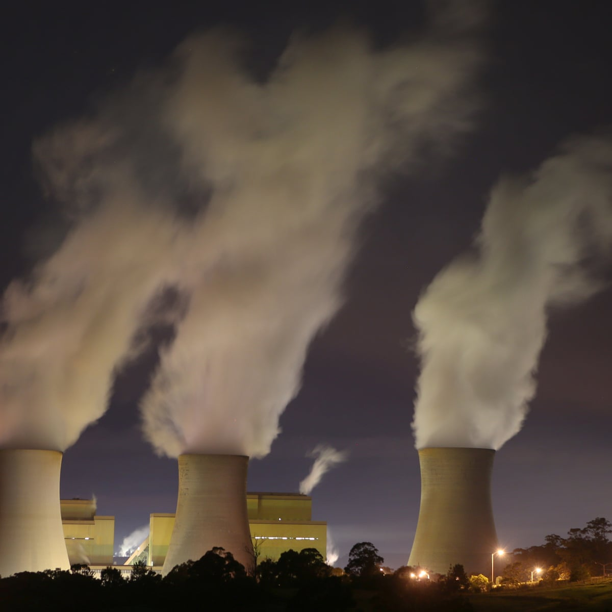 Long, ominous shot of factories emitting green house gases amongst trees