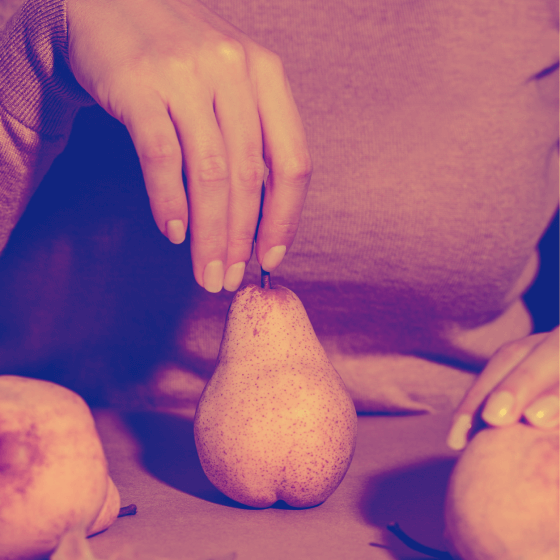 A woman holding the stem of a pear.