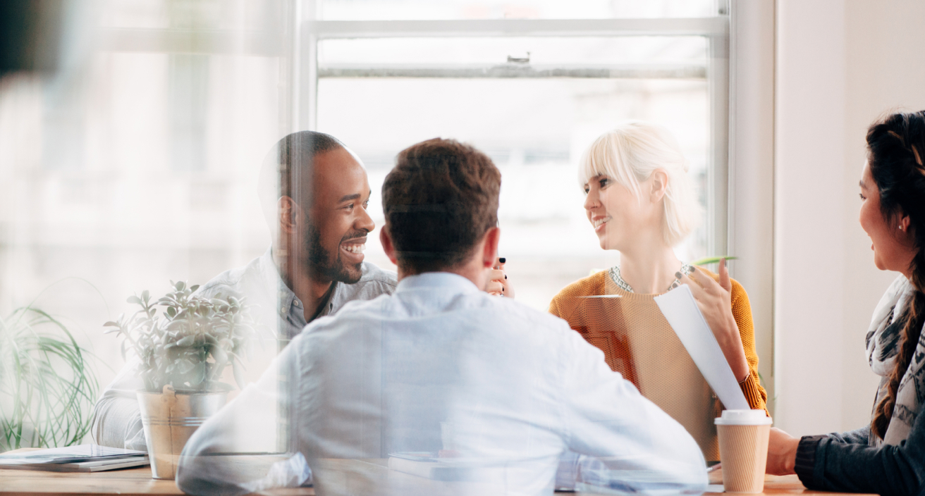 Four employees laughing while having a conversation