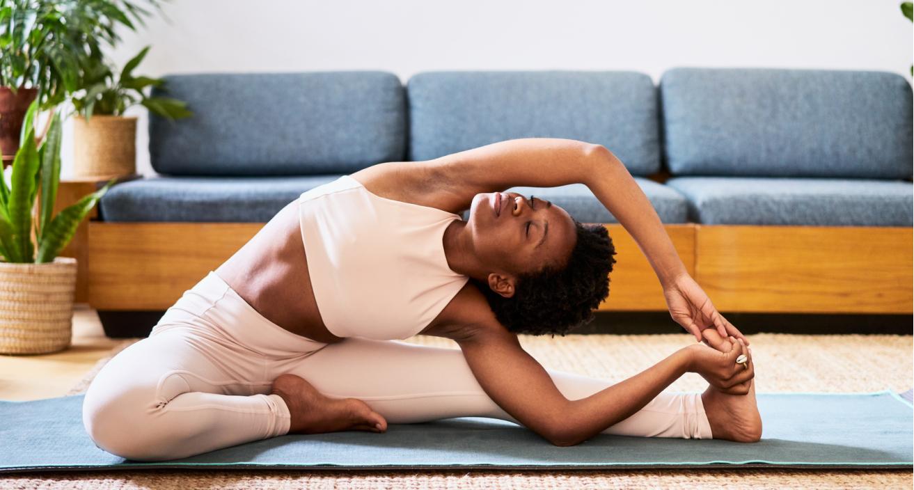 Woman on a yoga mat doing a side stretch