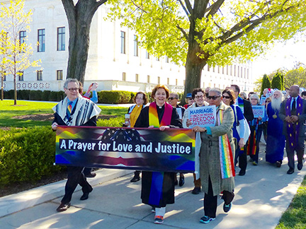 Rabbi Jack Moline and faith leaders holding various signs, including a large sign that says A Prayer for Love and Justice. They are walking along a sidewalk.