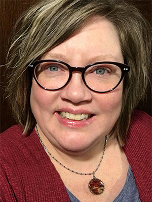 Headshot of Kristin, a smiling white woman with blond highlighted brown hair, wearing a burgundy sweater, a burgundy and khaki round necklace, and horn-rimmed glasses