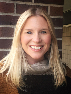 Headshot of Bridget, a smiling white woman with long blond hair, wearing a sweater in various shades of brown