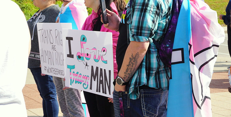 Torso shot of four people carrying signs affirming transgender rights