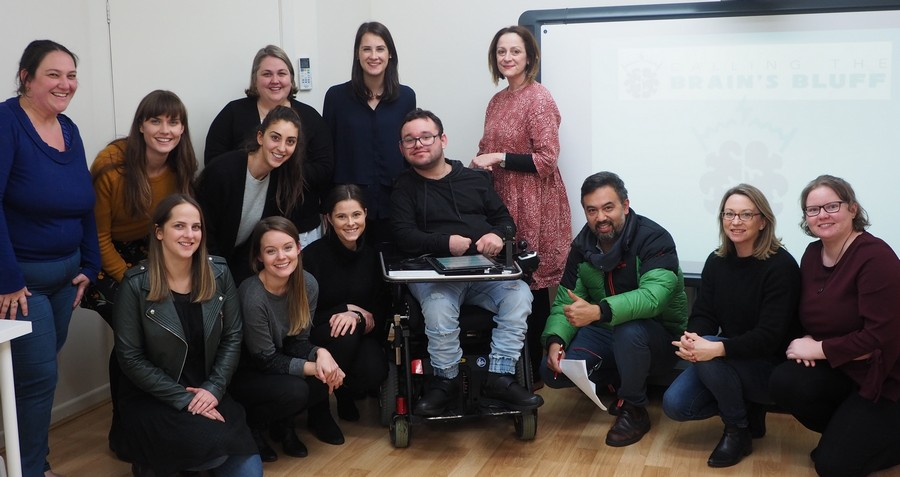 Image description: Jono with a group of speech pathologists after giving a presentation.