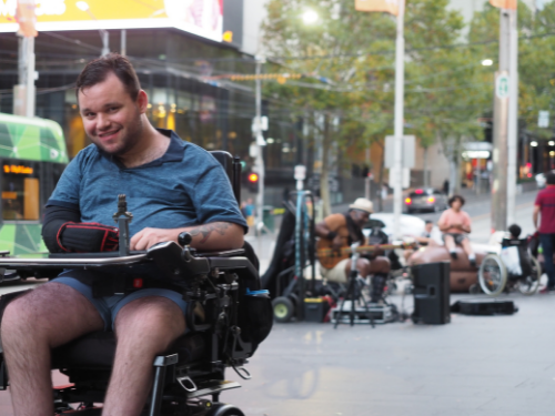 Image description: Jono in the Bourke St Mall Melbourne. Jono is smiling in front of a group of buskers, a tram is passing by.