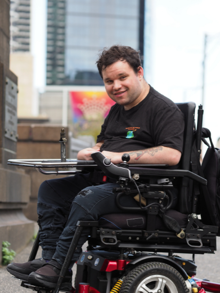 Image description: Jono smiling in his wheelchair in the city. There are high rises behind him.