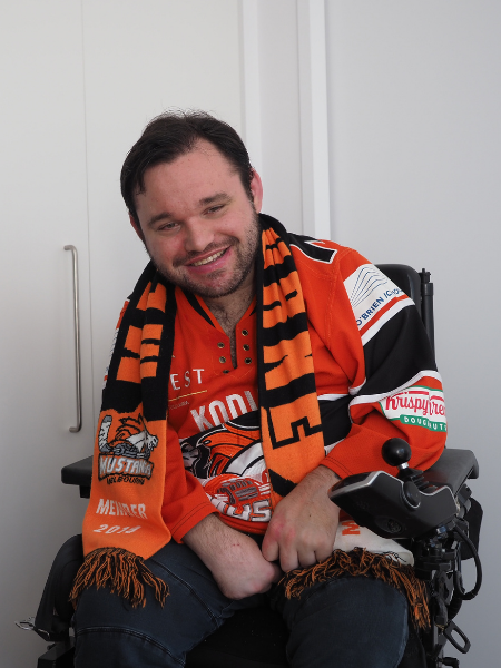 Image description: Jono dressed up in his Melbourne Mustangs jersey and scarf before heading to a game.