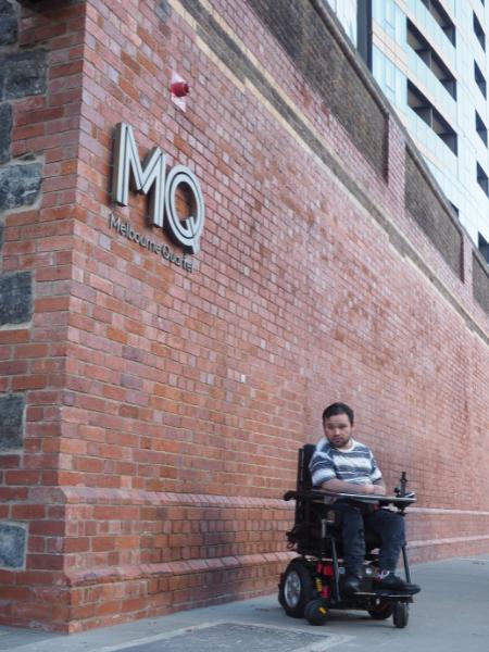 Image description: Jono in his wheelchair next to a brick wall.