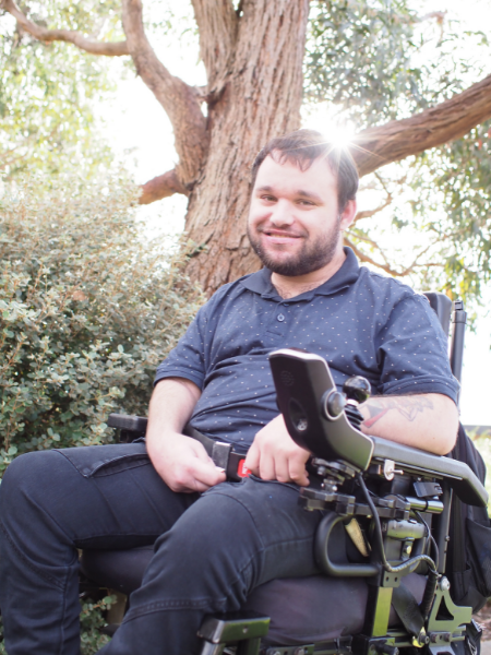 Image description: Jono in his wheelchair in a garden. There is a large tree behind him and the sun is shining through the branches.