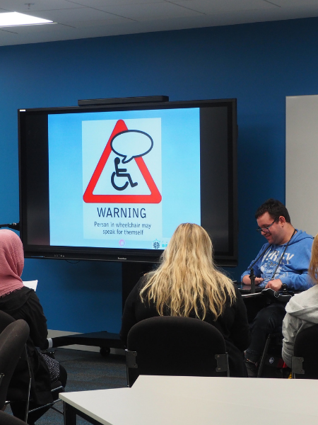 Image description: Jono giving a presentation on the NDIS at the Chisolm Institute.