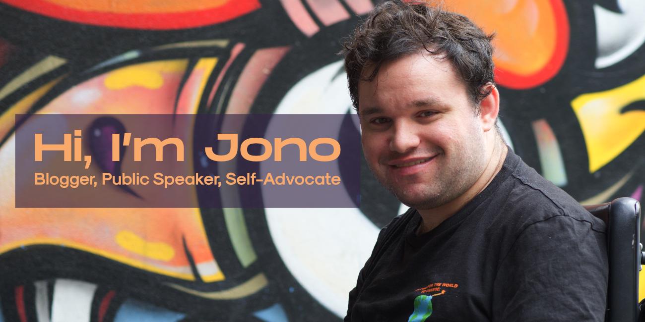 Hi, I'm Jono. Blogger, public speaker and self-advocate. Image description: Photograph of Jono smiling in front of a wall of graffiti.