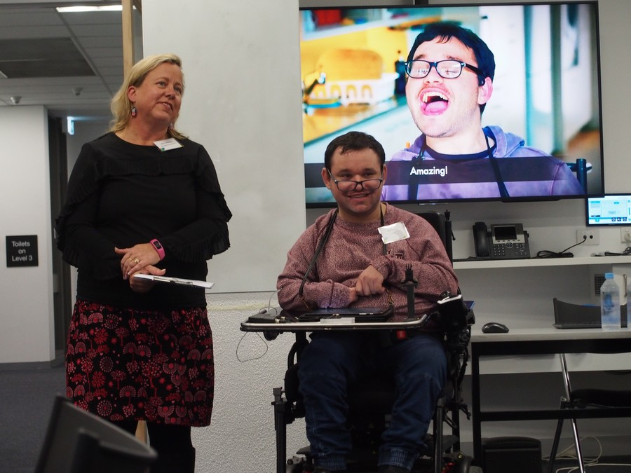 Image description: Jono giving a presentation. A woman is standing next to him.