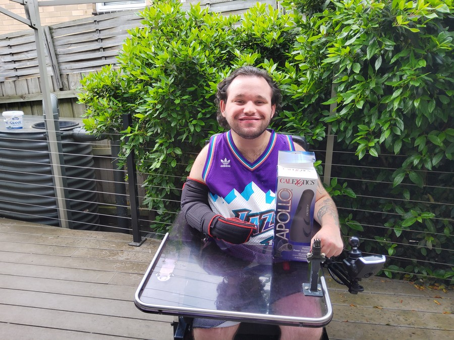 Image description: Jono in his wheelchair holding his new self-stimulation device. He is smiling and appears chuffed.