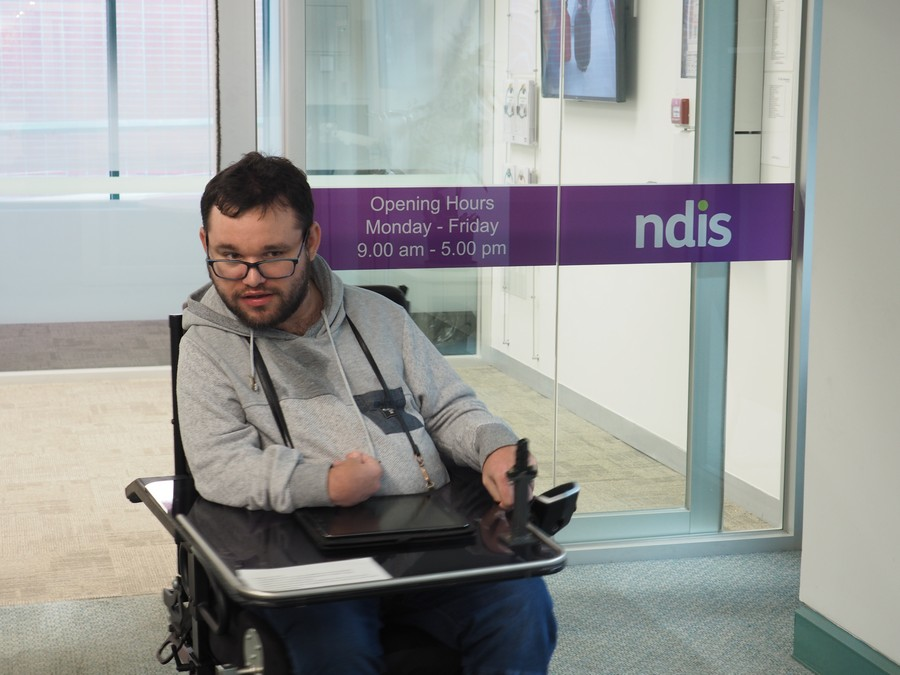 Image description: Jono exiting out the NDIS doors in his wheelchair.
