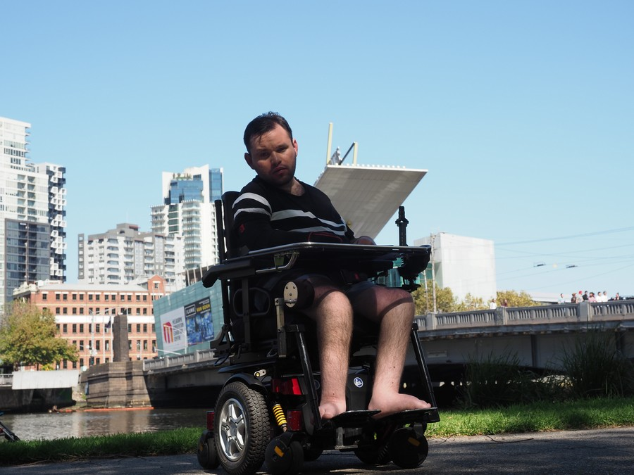 Image description: Jono in wheelchair, wearing black and white striped T-shirt with city landscape in the background.