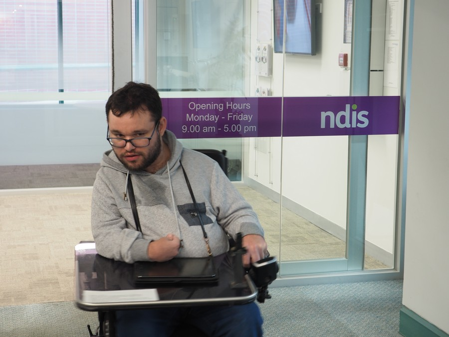 Image description: Jono in wheelchair in grey hoodie and exiting an NDIS office.