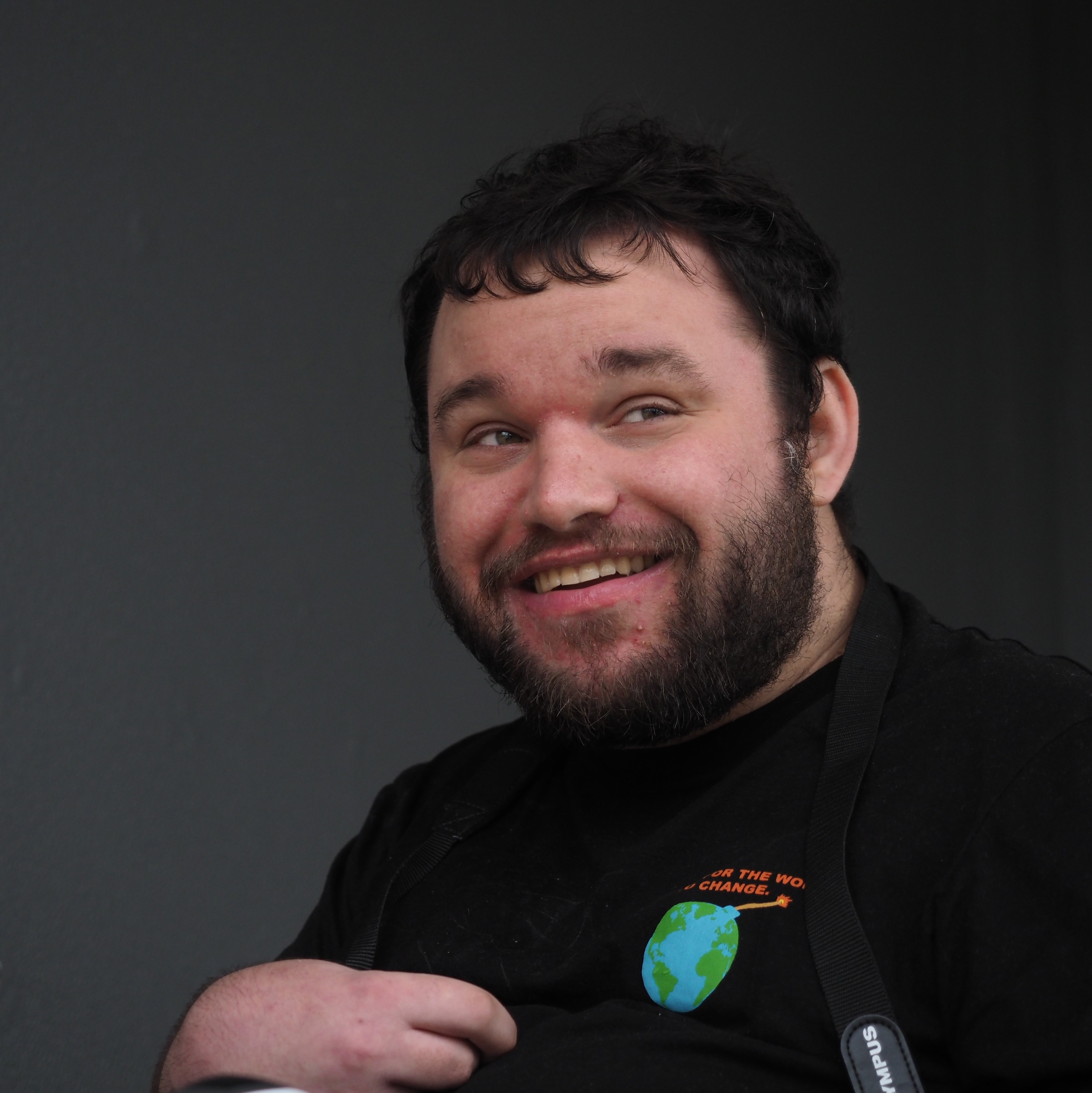 Image description: Jono glancing to his left and smiling in front of a black wall, his t-shirt has a logo that says 'waiting for the world to change',
